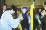 """Paiknam"" Kim Lyun-joon passing the school banner to Dr. Kim Jong-ryang"